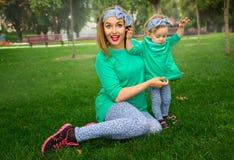 Счастливая мать играя с ее дочерью на траве Стоковые Изображения RF