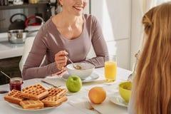 Счастливая мать имея завтрак с ее ребенком стоковое изображение