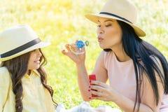 Счастливая мать имея playtime с ее ребенком на луге Стоковые Фото