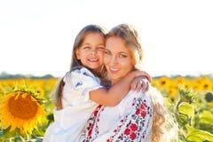 Счастливая мать и ее маленькая дочь в солнцецвете field Стоковая Фотография