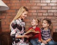 Счастливая мать и ее маленькие дочери внутри помещения. Предпосылка кирпича Стоковые Изображения RF