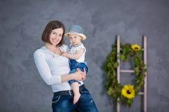 Счастливая мать и ее молодая дочь имеют потеху Они оба смеясь над Они имеют вскользь одежды и флористический wreathes o Стоковое Изображение RF