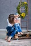 Счастливая мать и ее молодая дочь имеют потеху Они оба смеясь над Они имеют вскользь одежды и флористический wreathes o стоковое фото