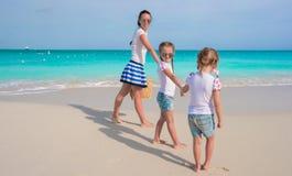 Счастливая мать и ее прелестные девушки имея потеху на тропическом пляже Стоковые Изображения RF