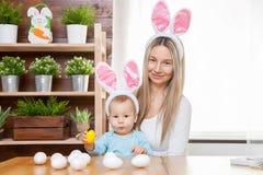 Счастливая мать и ее уши зайчика милого ребенка нося, получая готовый для пасхи Стоковые Фотографии RF