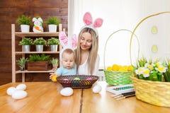 Счастливая мать и ее уши зайчика милого ребенка нося, получая готовый для пасхи Стоковые Изображения