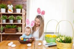 Счастливая мать и ее уши зайчика милого ребенка нося, получая готовый для пасхи Стоковые Изображения RF