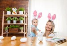 Счастливая мать и ее уши зайчика милого ребенка нося, получая готовый для пасхи Стоковая Фотография
