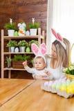 Счастливая мать и ее уши зайчика милого ребенка нося, получая готовый для пасхи Стоковое Фото