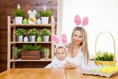 Счастливая мать и ее уши зайчика милого ребенка нося, получая готовый для пасхи Стоковая Фотография RF