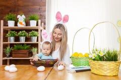 Счастливая мать и ее уши зайчика милого ребенка нося, получая готовый для пасхи Стоковое Изображение RF