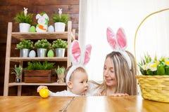 Счастливая мать и ее уши зайчика милого ребенка нося, получая готовый для пасхи Стоковые Фото