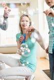 Счастливая мать и дети играя с палочками пузыря дома Стоковое Изображение
