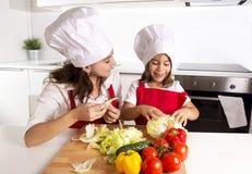 Счастливая мать и маленькая кухня дочери дома подготавливая салат в шляпе рисбермы и кашевара Стоковое Фото