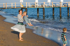 Счастливая мать и 2 маленьких дет идя на пляж Стоковые Изображения RF