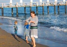 Счастливая мать и 2 маленьких дет идя на пляж Стоковая Фотография