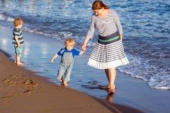 Счастливая мать и 2 маленьких дет идя на пляж Стоковые Изображения