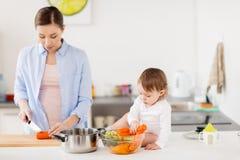 Счастливая мать и младенец варя кухню еды дома Стоковая Фотография