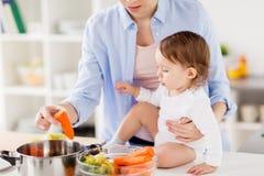 Счастливая мать и младенец варя овощи дома Стоковая Фотография