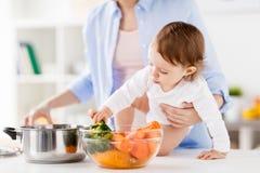 Счастливая мать и младенец варя овощи дома Стоковые Изображения