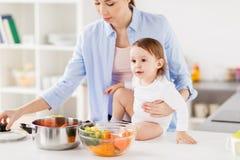 Счастливая мать и младенец варя овощи дома Стоковое фото RF