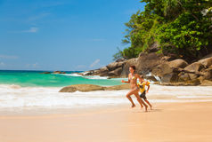 Счастливая мать и дочь бежать на пляже Стоковые Изображения