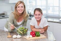 Счастливая мать и дочь подготавливая салат совместно Стоковая Фотография RF