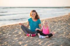 Счастливая мать и дочь сидя в положении лотоса на пляже Стоковая Фотография
