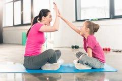 Счастливая мать и дочь сидя на циновке йоги и давая максимум 5 в спортзале Стоковые Изображения RF