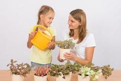 Счастливая мать и дочь смотря один другого моча цветки Стоковое Фото