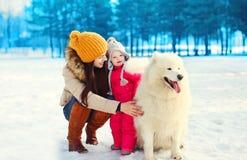 Счастливая мать и ребенок идя с белой собакой Samoyed в зиме Стоковое Изображение RF