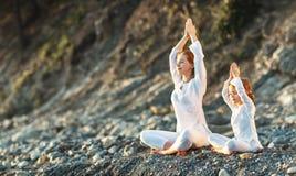 Счастливая мать и ребенок семьи делая йогу, размышляют в posi лотоса Стоковая Фотография