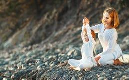 Счастливая мать и ребенок семьи делая йогу, размышляют в posi лотоса Стоковые Изображения RF
