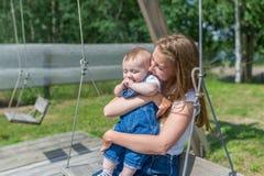 Счастливая мать и смеясь над сын на качании в парке Стоковое Изображение