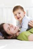 Счастливая мать и сын играя и имея потеху в кровати. стоковое фото rf