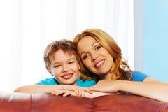 Счастливая мать и сын обнимая дома Стоковые Фото