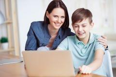 Счастливая мать помогая его сыну сделать домашнюю работу Стоковое Изображение