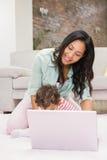 Счастливая мать при ее младенец используя компьтер-книжку Стоковое фото RF
