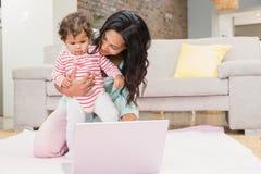 Счастливая мать при ее младенец используя компьтер-книжку Стоковые Изображения RF