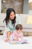 Счастливая мать при ее младенец смотря книгу Стоковые Фото
