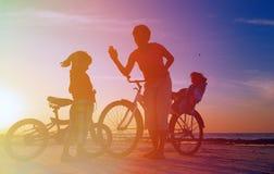 Счастливая мать при 2 дет велосипед на заходе солнца Стоковые Изображения RF