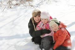 Счастливая мать при 2 дет лежа в снеге Стоковые Изображения RF
