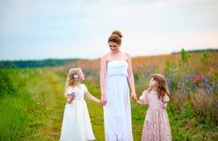 Счастливая мать при 2 дет идя около маков field Стоковое Изображение