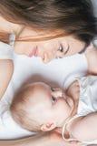 Счастливая мать при младенец лежа на белой кровати Стоковые Изображения RF