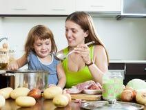 Счастливая мать при дочь варя совместно Стоковое фото RF