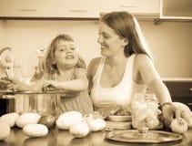 Счастливая мать при дочь варя суп Стоковое Фото