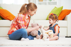 Счастливая мать семьи и девушка ребенка дочери играя с игрушкой ted Стоковые Изображения