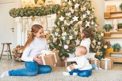 Счастливая мать семьи и 2 дет на дереве утра рождества Стоковые Изображения RF