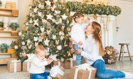 Счастливая мать семьи и 2 дет на дереве утра рождества Стоковые Фотографии RF