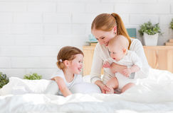 Счастливая мать семьи и 2 дет, сын и дочь в кровати Стоковые Фото